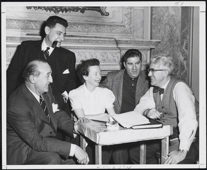 A 1954 photograph from the Museum of the City Of New York of an elite group of theatrical legends with songwriter Leo Robin. Standing is lyricist Leo Robin and sitting around the table  from left to right: playwright and stage director Joseph Fields, dancer and choreographer Agnes De Mille (Her father William C. deMille and her uncle Cecil B. DeMille were both Hollywood directors.), playwright and librettist Jerome Chodorov and stage director and producer Shepard Traube