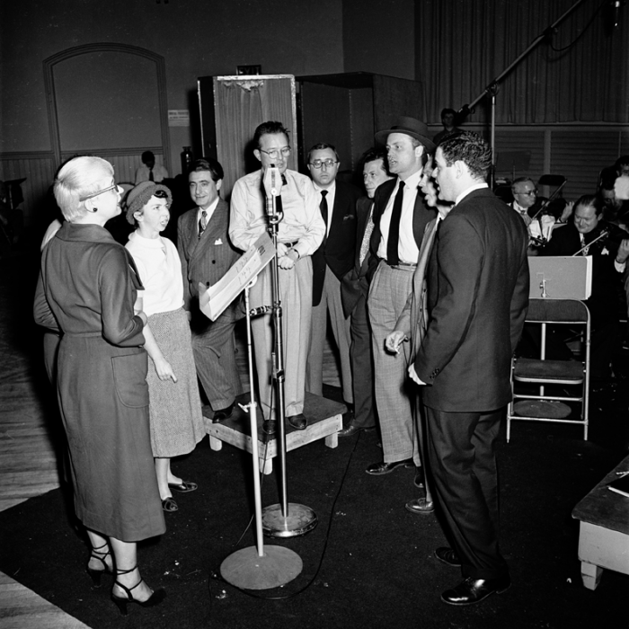 Backstage on the set of Gentlemen Prefer Blondes in 1949. From left to right: Carol Channing, Alice Pearce, lyricist Leo Robin, show producer Herman Levin, and other members of the cast -- Manny Sachs, Eric Brotherson, Jack McCauley, and George S. Irving listening to Jule Styne at the microphone.