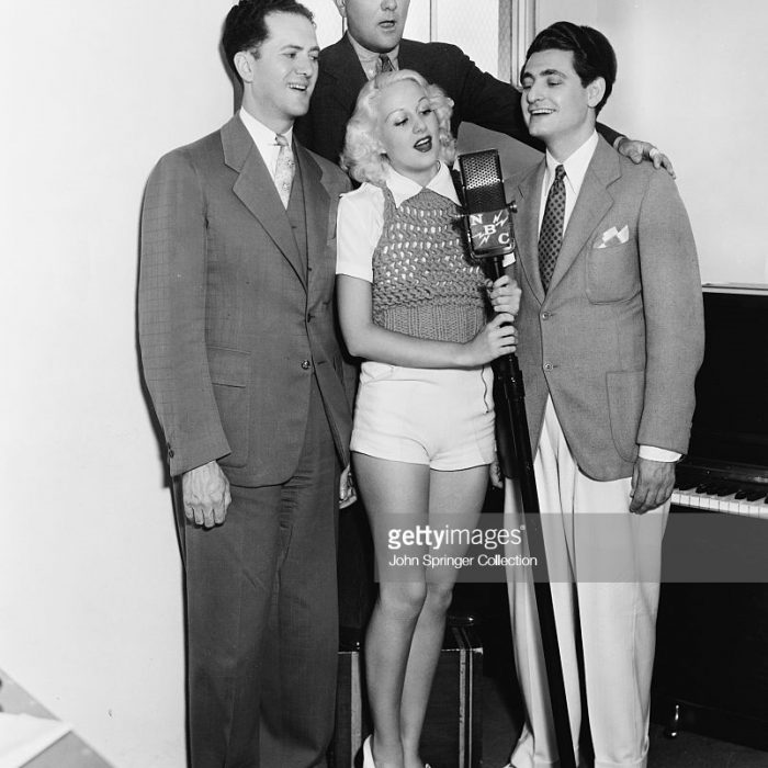 Songwriters singing into NBC microphone. From left to right: Composer Ralph Rainger, Composer Richard Whiting and Lyricist Leo Robin practice a song with one of the dancers from the film The Big Broadcast of 1936