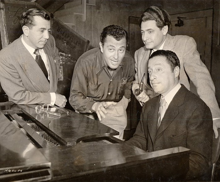 On the set of Casbah.  Around the piano, from left to right: producer Nat Goldstone, actor-singer Tony Martin, lyricist Leo Robin and composer Harold Arlen.