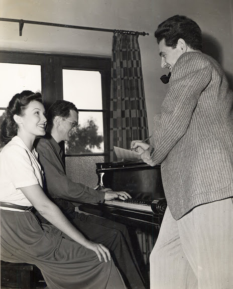 Leo Robin and Ralph Rainger at the piano with actress and dancer, Eleanore Whitney, in their bungalow on the Paramount lot, rehearsing a song for College Holiday, 1936.