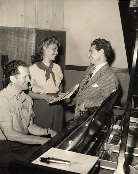 Leo Robin and Ralph Rainger with singer-actress Dinah Shore rehearsing at a recording studio.