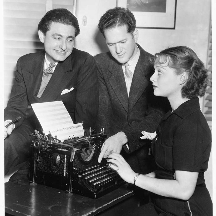 Leo Robin and Ralph Rainger with actress and dancer, Eleanore Whitney, try out the tune typing machine, a revolutionary score-writing machine, with some new songs for Three Cheers for Love, in which Miss Whitney starred