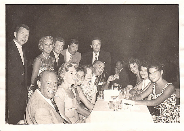 """Leo Robin at the Hollywood Palladium on July 29, 1955 with family and friends and the Palladium bandleader performing that evening, who came over to the table and joined the group. Standing from left to right: 1st-friend, 2nd-Fran Robin (Leo's wife), 3rd-Leo, 4th-Harry Warren's son-in-law, 5th-Gus Bivona (Leo's brother-in-law and first clarinetist as well as the bandleader of the MGM Orchestra; he became television host Steve Allen's sidekick). Seated from left to right: 1st-Lou Singer (Leo's brother-in-law and a songwriter who wrote the famous depression anthem, """"One Meatball"""